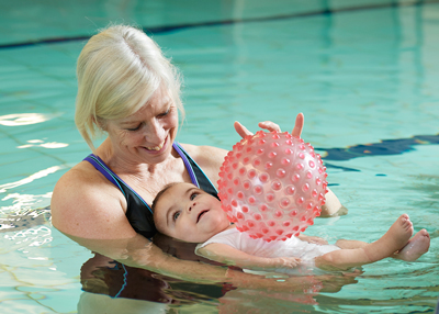 Physio in pool with patient and ball