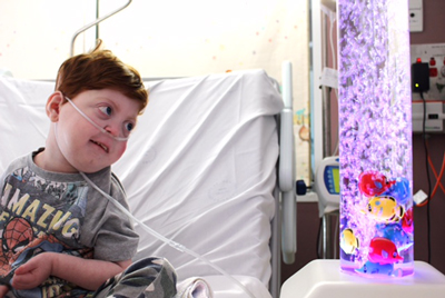 Child in hospital bed smiling while looking at fish in bubble tube